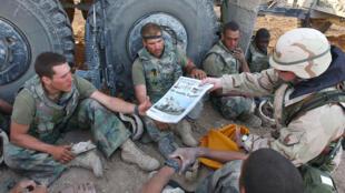 Sur cette image publiée par la marine américaine le 7 avril 2003, le sergent-chef John Sparks livre des copies de Stars and Stripes aux marines américains du peloton d'armes de la 3-2 India Company.