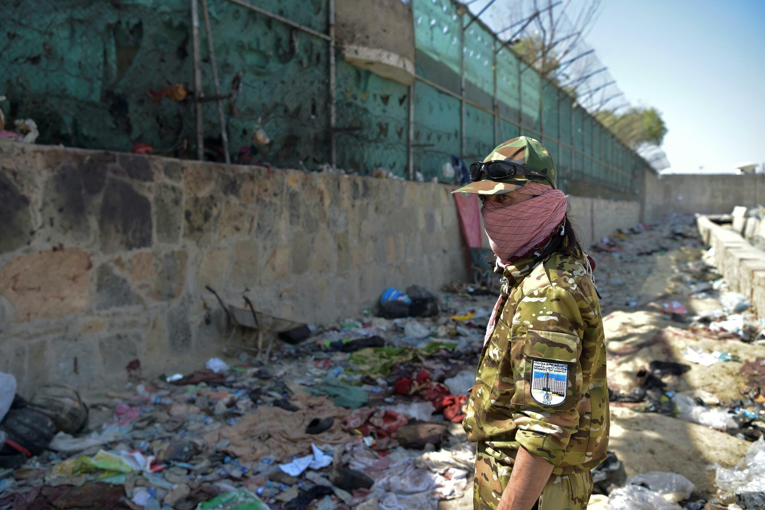 A Taliban fighter stands guard at the site of the deadly suicide attack at Kabul airport