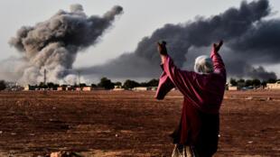Do lado turco da fronteira, mulher observa combates em Kobane, na Síria.