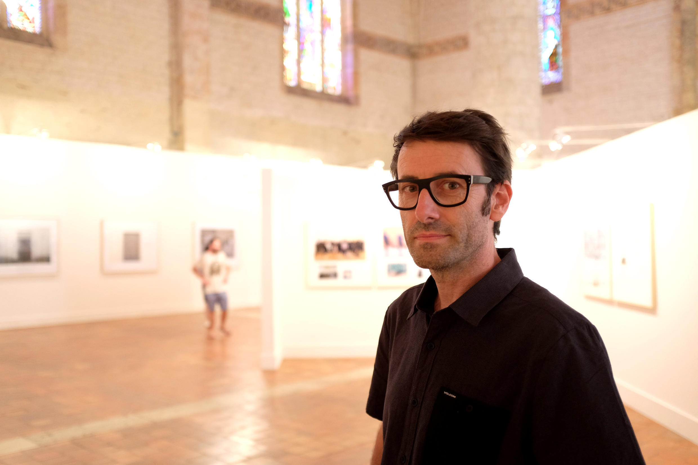 L'artiste photographe Arnaud Théval dans son exposition « L'œilleton inversé » à l'Eglise des Jacobins, à Agen.