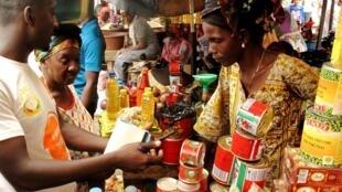Les concepteurs de M-Makiti présentent leur nouveau service dans le marché de Pharmaguinée près de Madina à Conakry.