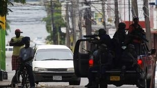 Armed police question men on the street in the market area near Tivoli Gardens neighborhood of Kingston, Jamaica