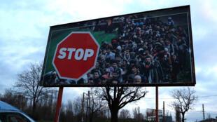 Un panneau électoral du Fidesz, le parti au pouvoir : une foule de visages noirs barrée par un «stop» en lettres rouges.