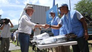 El presidente de Colombia, Juan Manuel Santos, saluda a un observador de la ONU antes de cerrar el contenedor con los últimos fusiles de las FARC el 15 de agosto de 2018.