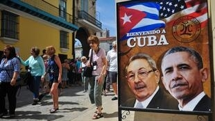 Watalii wakipita nyuma ya bango linaloadhimisha ujio wa Barack Obama. Havana, Machi 18 2016.