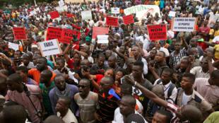 Des manifestations brandissent des pancartes dénonçant des fraudes supposées lors du premier tour l'élection présidentielle malienne, à Bamako, à la veille du second tour, le 11 août 2018.