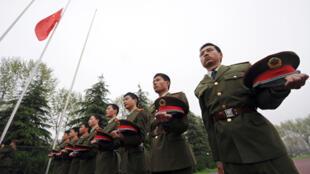 Des soldats stagiaires chinois de l'université de Hefei dans la province de Anhui, observent trois minutes de silence devant le drapeau national en berne, le 21 avril 2010.