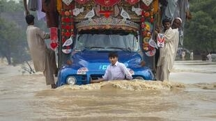 A boy hangs on to the front of a cargo truck while passing through a flooded road in Risalpur in Pakistan's Northwest Frontier Province