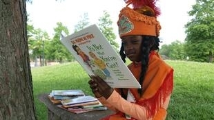 Little Queen Malon McKee of the Guardians of the Flame Maroon Society spreading the love of reading to New Orleans children