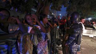 """Haitianos esperan frente al Ministerio del Interior, rodeados de policiías, para registrarse en el programa de """"regularización"""", Santo Domingo, 17 de junio de 2015."""