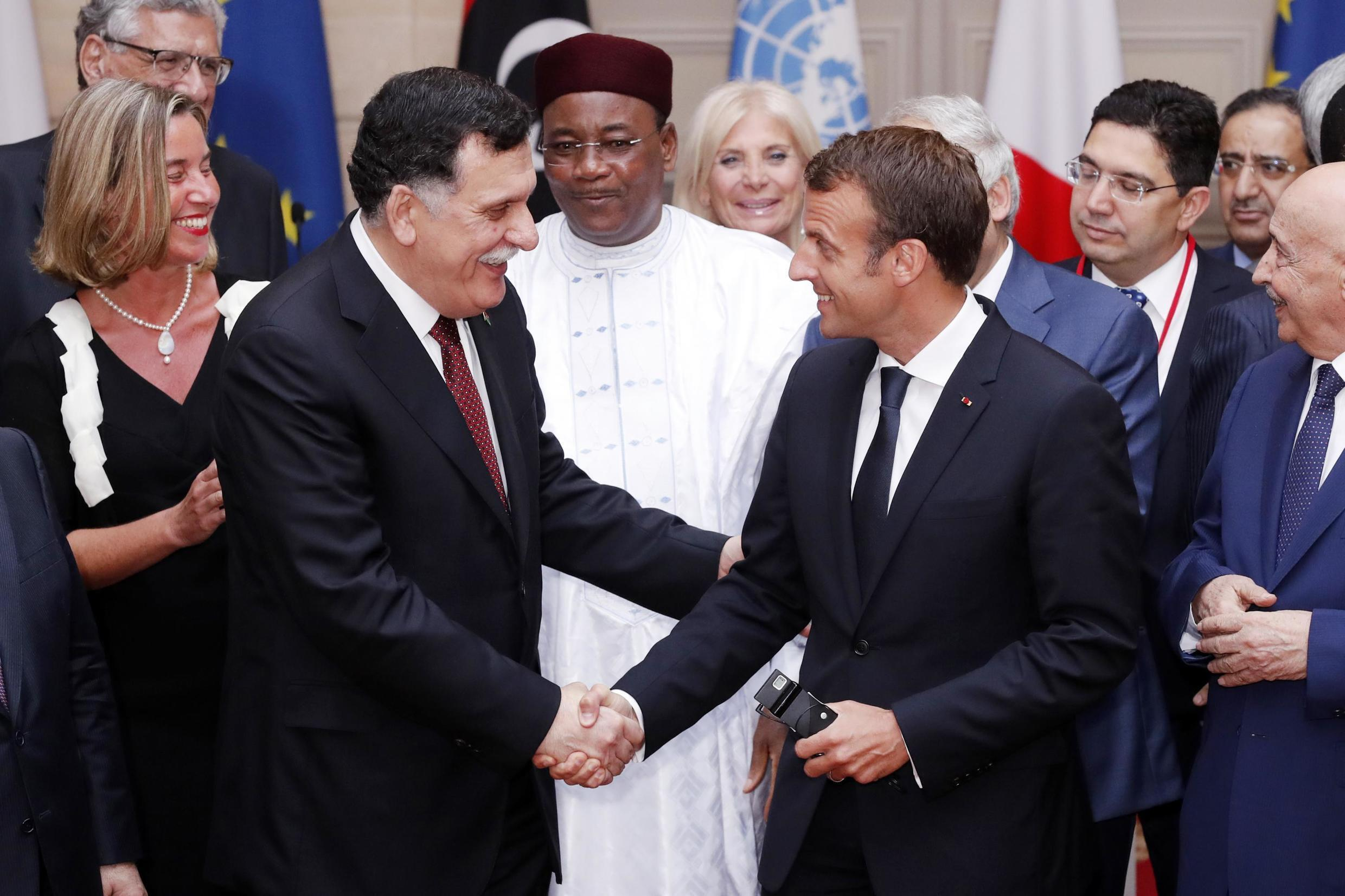 Prime Minister Fayez al-Sarraj shakes hands with French President Emmanuel Macron at International Conference on Libya at the Elysee Palace in Paris, 29 May 29 2018.