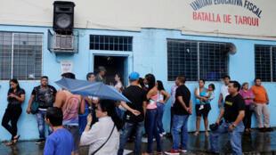 图为厄瓜多尔总统选举选民在一所学校投票站排队投票