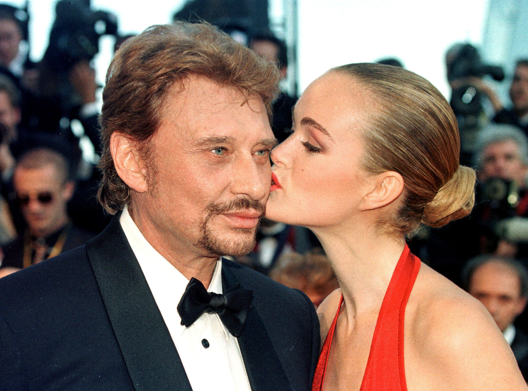French singer Johnny Hallyday is kissed by his wife Laeticia as they arrive for the opening of the 51st Cannes Film Festival in Cannes, May 13, 1998.
