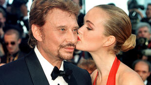 rench singer Johnny Hallyday is kissed by his wife Laeticia as they arrive for the opening of the 51st Cannes Film Festival in Cannes, France, May 13, 1998.