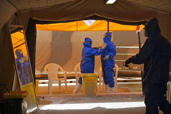 Ebola : « les ¾ des rescapés déclarent encore avoir des symptômes plusieurs mois après la fin de l'épidémie. »  (Ici, le personnel soignant se protège avant de traiter les malades).