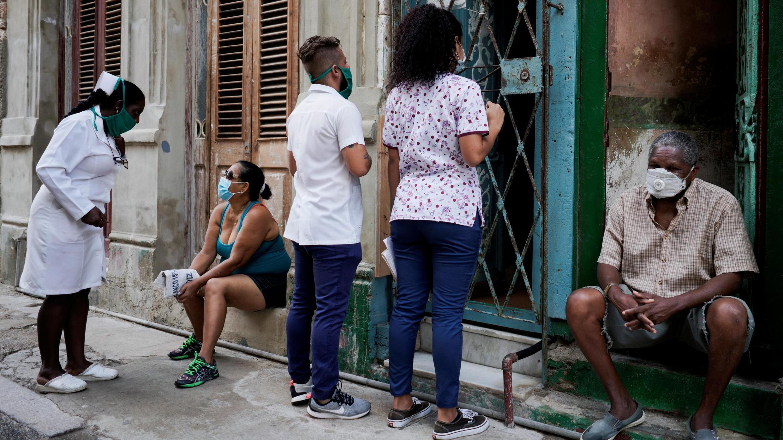 Des étudiants en médecine font du porte-à-porte à la recherche de personnes qui présenteraient des symptômes du Covid-19, afin de stopper la propagation de l'épidémie. Photo prise à La Havane, Cuba, le 11 mai 2020.