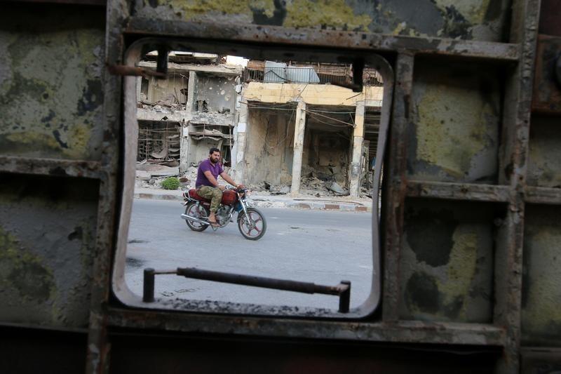 Một người dân chạy xe trên một con phố ở Aleppo, gần các tòa nhà đã bị không kích.