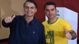 Jair Bolsonaro e o filho Flávio Bolsonaro após votarem no primeiro turno da eleição presidencial brasileira, em 7 de outubro de 2018.