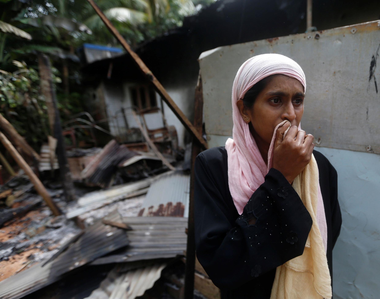 Une femme se tient devant sa maison brûlée, à Aluthgama (Sri Lanka), le 16 juin 2014.