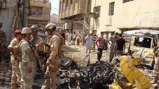 居民和士兵聚集在巴格達西北部一起汽車爆炸案現場. (2010/4/23)