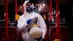 Un agent désinfecte un bus dans une station de lavage de bus de la société de transports de la ville de Bratislava dans le cadre des mesures de protection contre la propagation du Covid-19, le 11 mars 2020.