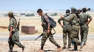 Des combattants kurdes à l'entrée est de la ville de Tal-Abyad, ce dimanche 14 juin 2015, après avoir pris le contrôle de Slok, une ville alentour.