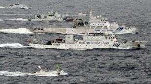 Photo aérienne d'un navire de surveillance chinois naviguant à proximité d'un bateau garde-côte japonais, dans l'est de la mer de Chine, non loin des iles Senkaku.