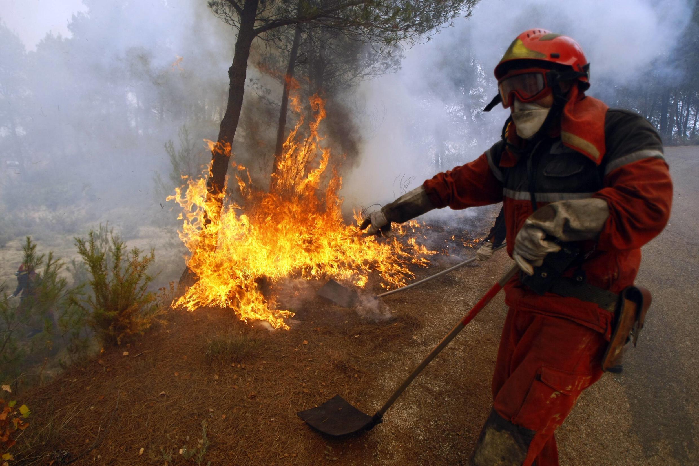 Bombeiro tenta controlar o fogo em Torremanzanas, perto de Alicante.