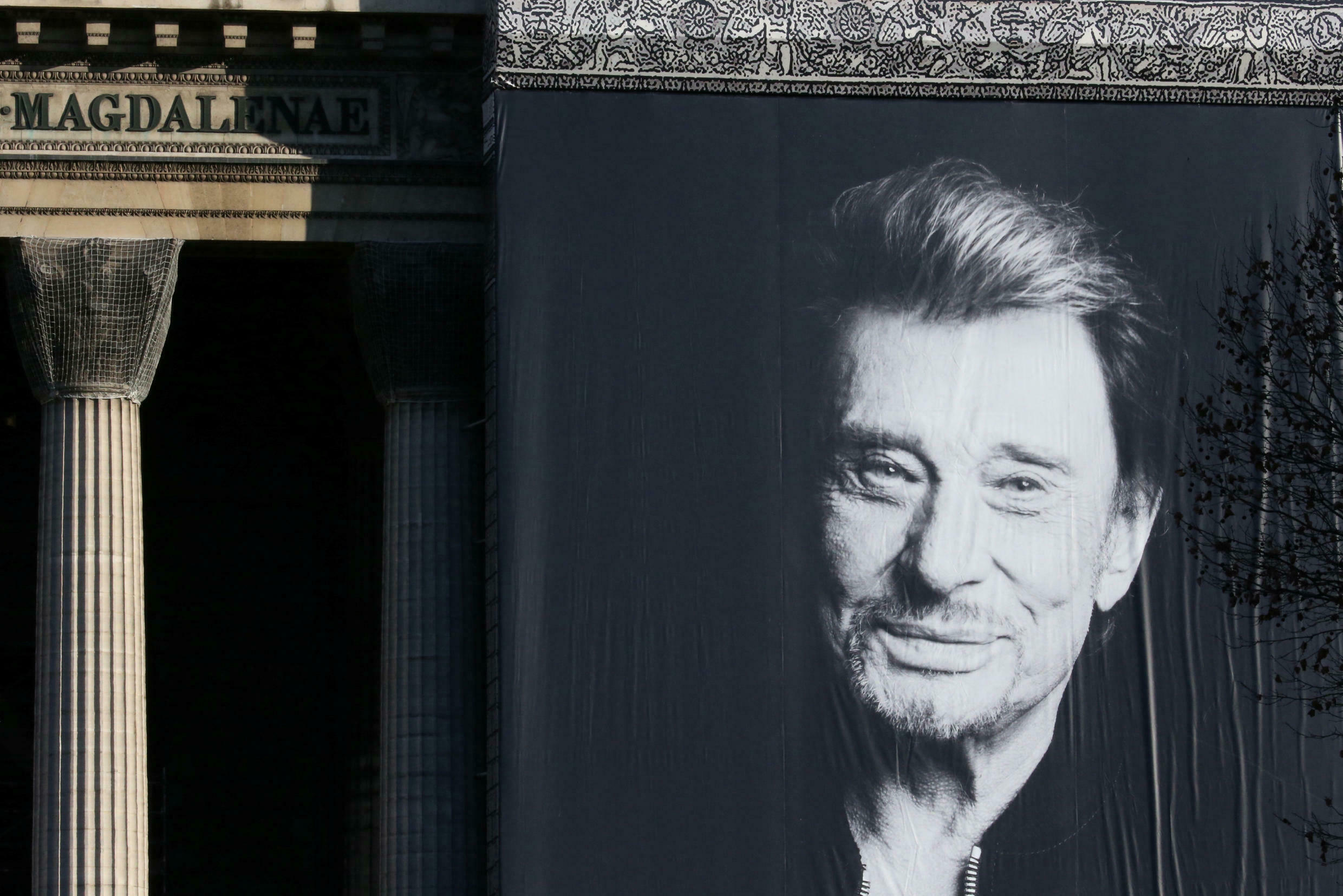 A giant poster of late French singer and actor Johnny Hallyday is displayed on the facade of the Madeleine Church during a ceremony in Paris, December 9, 2017.