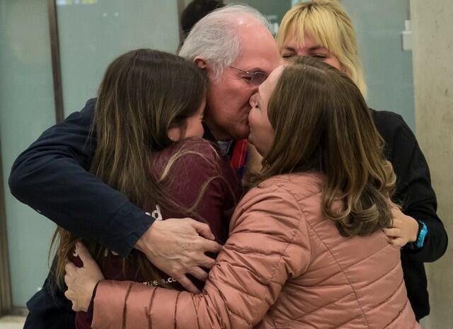 O prefeito opositor de Caracas, Antonio Ledezma, abraça a mulher e as filhas ao desembarcar neste sábado (18) em Madri.