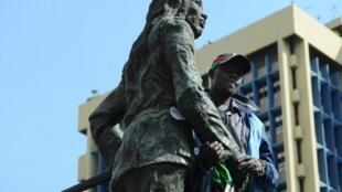 Nairobi, le 9 juin 2014. Dedan Kimathi Waceke enchaîné à la statue qui représente Dedan Kimathi, qui aurait été son grand-père, pour protester contre le faible intérêt porté par l'État à la descendance du leader Mau Mau.