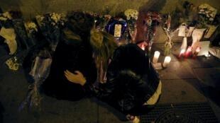 Duas mulheres se abraçam diante de velas e flores depositadas na frente da embaixada da França em Madri.