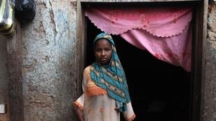 A Chadian Muslim girl at the doorway to her house in Bangui