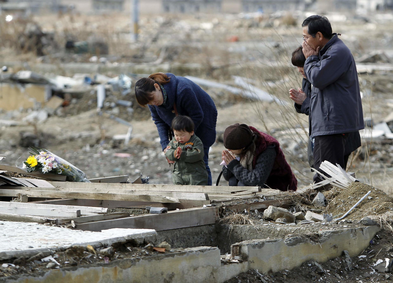 Família reza em homenagens a vítimas mortas na cidade de Ishinomaki.