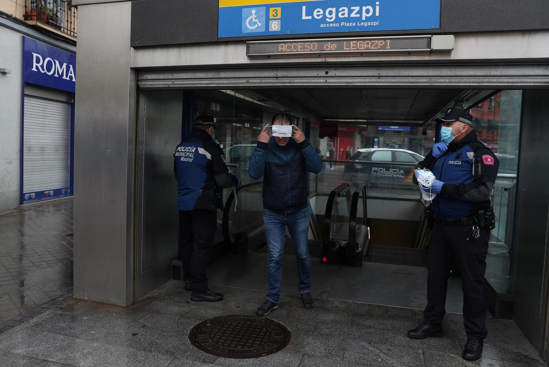 Polisi ikiwapa abiria marakoa kwenye vituo vya treni za mwendo kasi huko Madrid, Aprili 13, 2020.