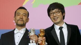 Le réalisateur chinois Diao Yinan (D) et l'acteur Liao Fan avec leurs récompenses obtenues pour le thriller «Black Coal, Thin Ice» à Berlin.