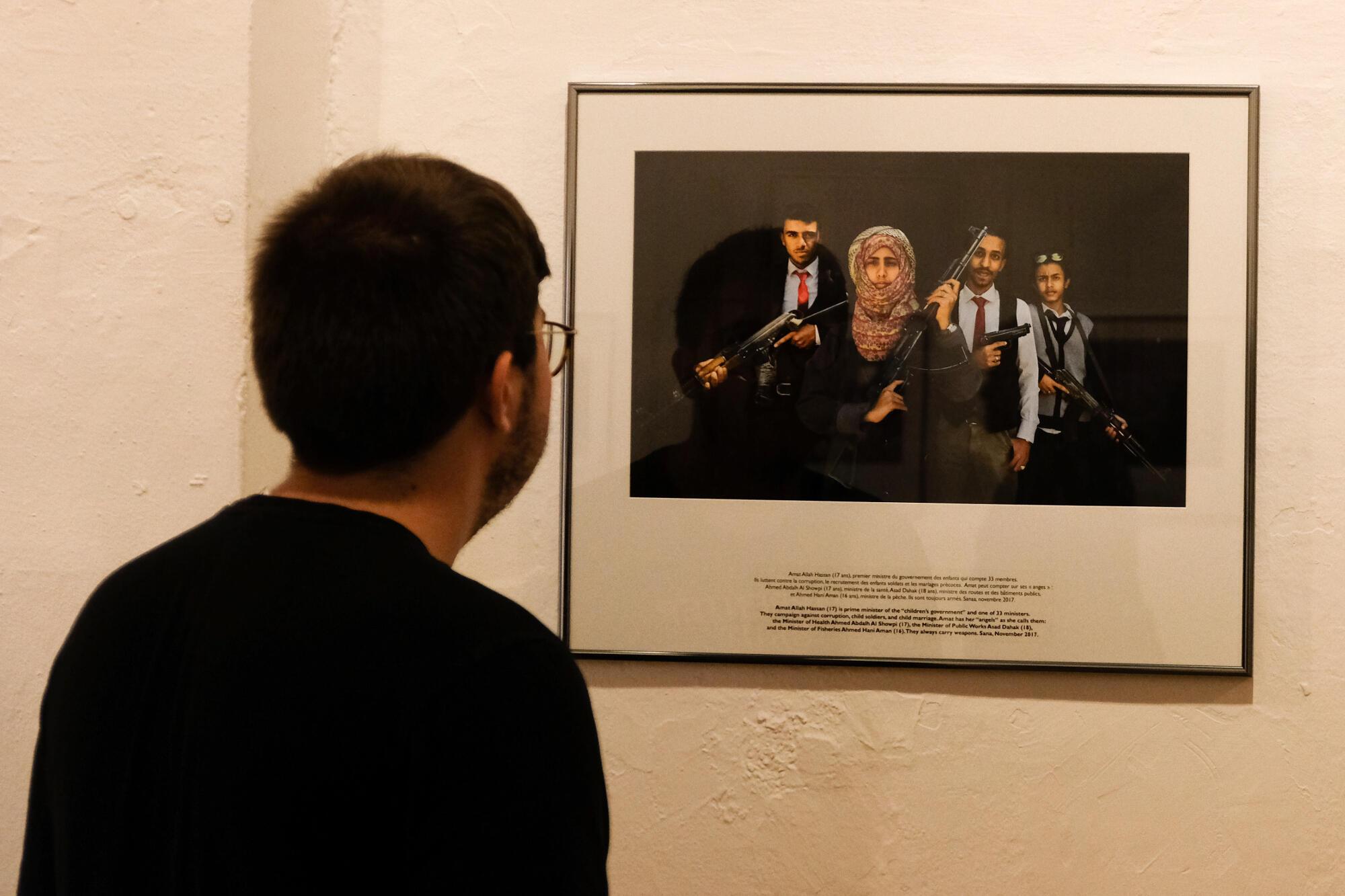Véronique de Viguerie a tiré le portrait d'Amat Allah Hassan, Première ministre du gouvernement des enfants, entourée de ses ministres, adolescents armés en costume-cravate.