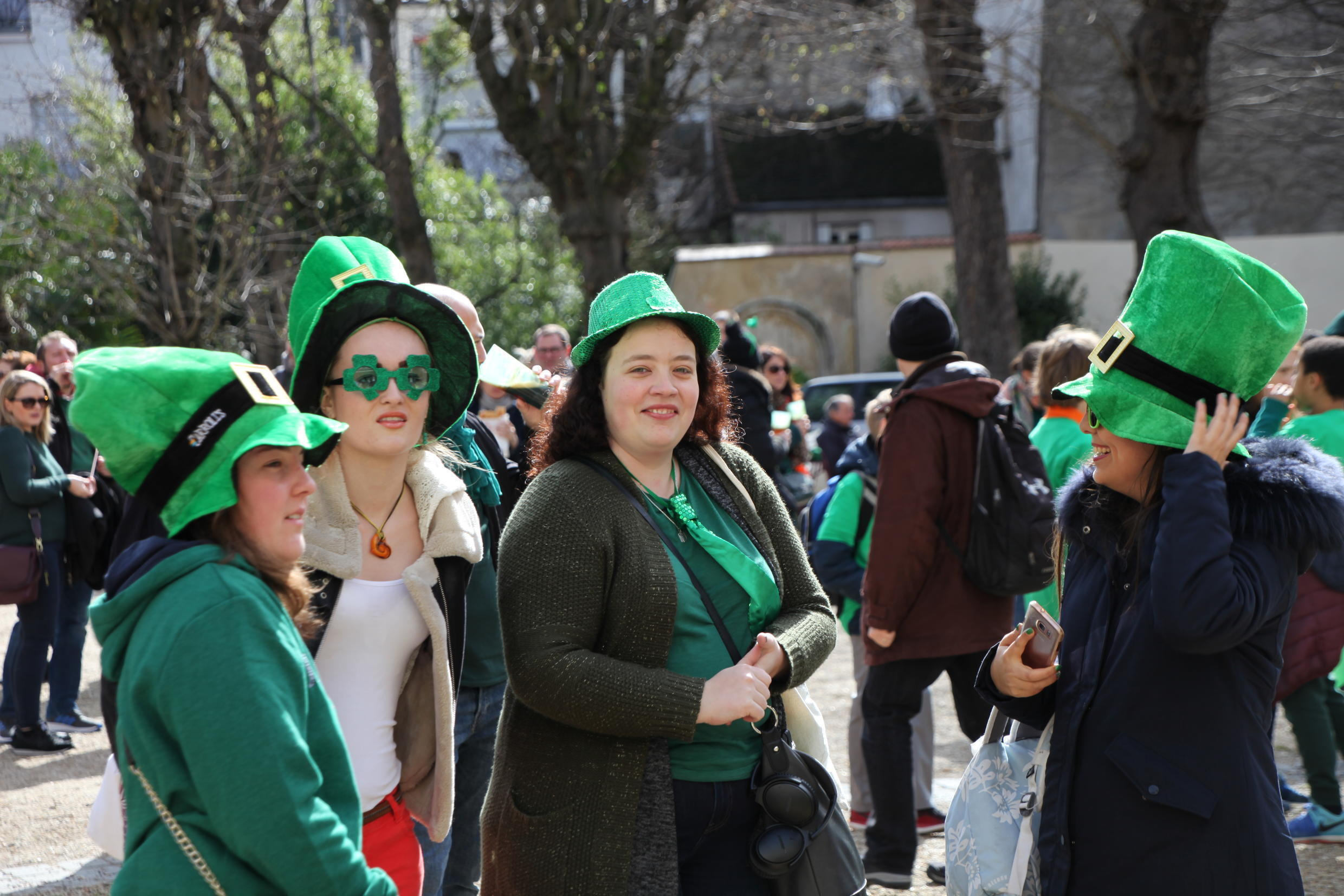 Dressed in green and wearing national symbols, people gather in the courtyard of the Irish Cultural Centre