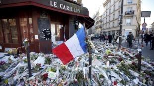 2015年11月13日巴黎第十區遭遇恐怖襲擊的一家酒吧門前的紀念鮮花與法國三色旗。圖片攝於2015年11月22日