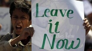 A boy holds a sign during an-anti government protest in Sanaa, 23 February 2011