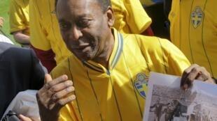 Pelé exibe foto da conquista do título de campeão de 1958, durante visita o estádio Rasunda, nesta terça-feira, 14 de agosto.
