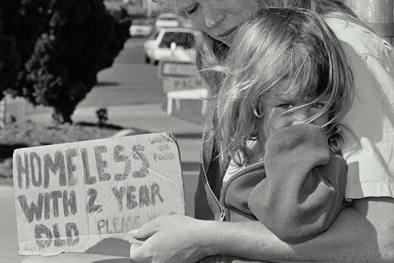 Une mère sans-abri avec son enfant de 2 ans 'fait la manche', «<i>du travail ou de la nourriture</i>, a-t-elle inscrit sur sa pancarte.