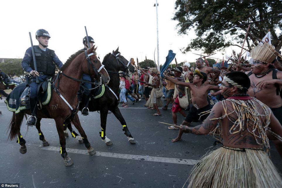 Imagem impressionante de índios brasileiros diantes de militares a cavalo nos protestos de 27 de maio de 2014.