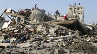 Palestinos procuram pertences em escombros de casa destruída por ataque israelense