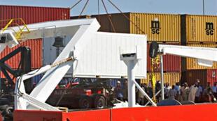 Débarquement, à Moroni le 14 septembre 2009, de conteneurs où se trouvent les restes humains de 59 des 152 victimes du crash de l'Airbus A-310 de la Yemenia.