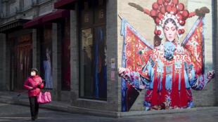 一名女子走過北京一處安靜的街拐角