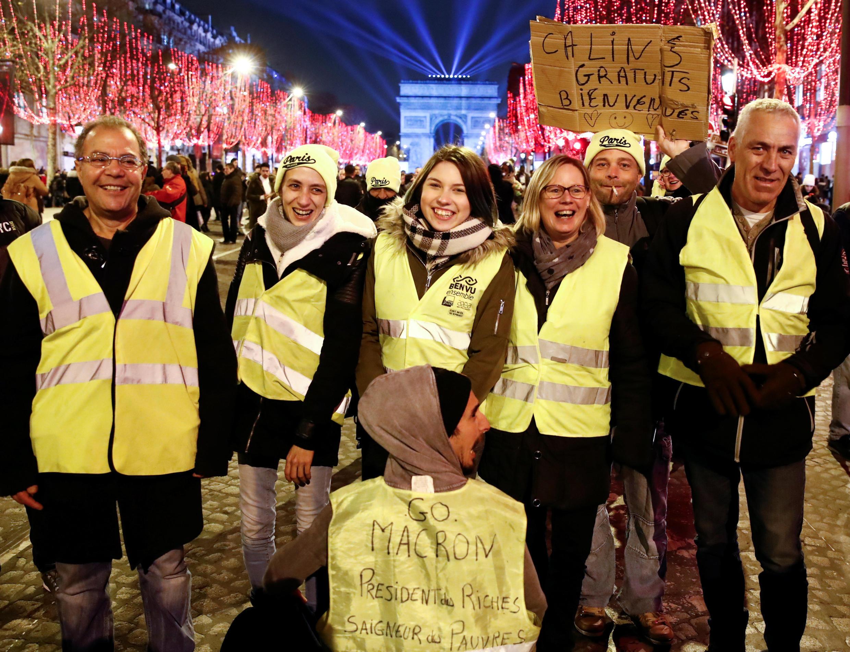 """""""Coletes amarelos"""" festejam Ano Novo na avenida Champs Élysées com mensagens para o presidente: """"Fora Macron, presidente dos ricos, assassino dos pobres; abraços gratuitos são bem-vindos""""."""
