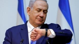 O primeiro-ministro israelense Benjamin Netanyahu olha para o relógio antes de fazer uma declaração no Knesset, o parlamento de Israel, em Jerusalém. 11/12/2019.