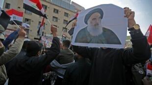 Manifestante exibindo cartaz do líder religioso xiita Ali Sistani, na praça Tahrir de Bagdade a 5 de dezembro de 2019