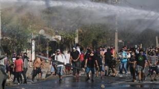 Des habitants d'une banlieue pauvre de Santiago protestent contre le manque de soutien du gouvernement en période de confinement, le 18 mai 2020.